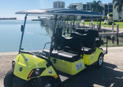 Empty yellow golf cart next to ocean
