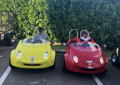 Two men riding in yellow and red scoot coupes