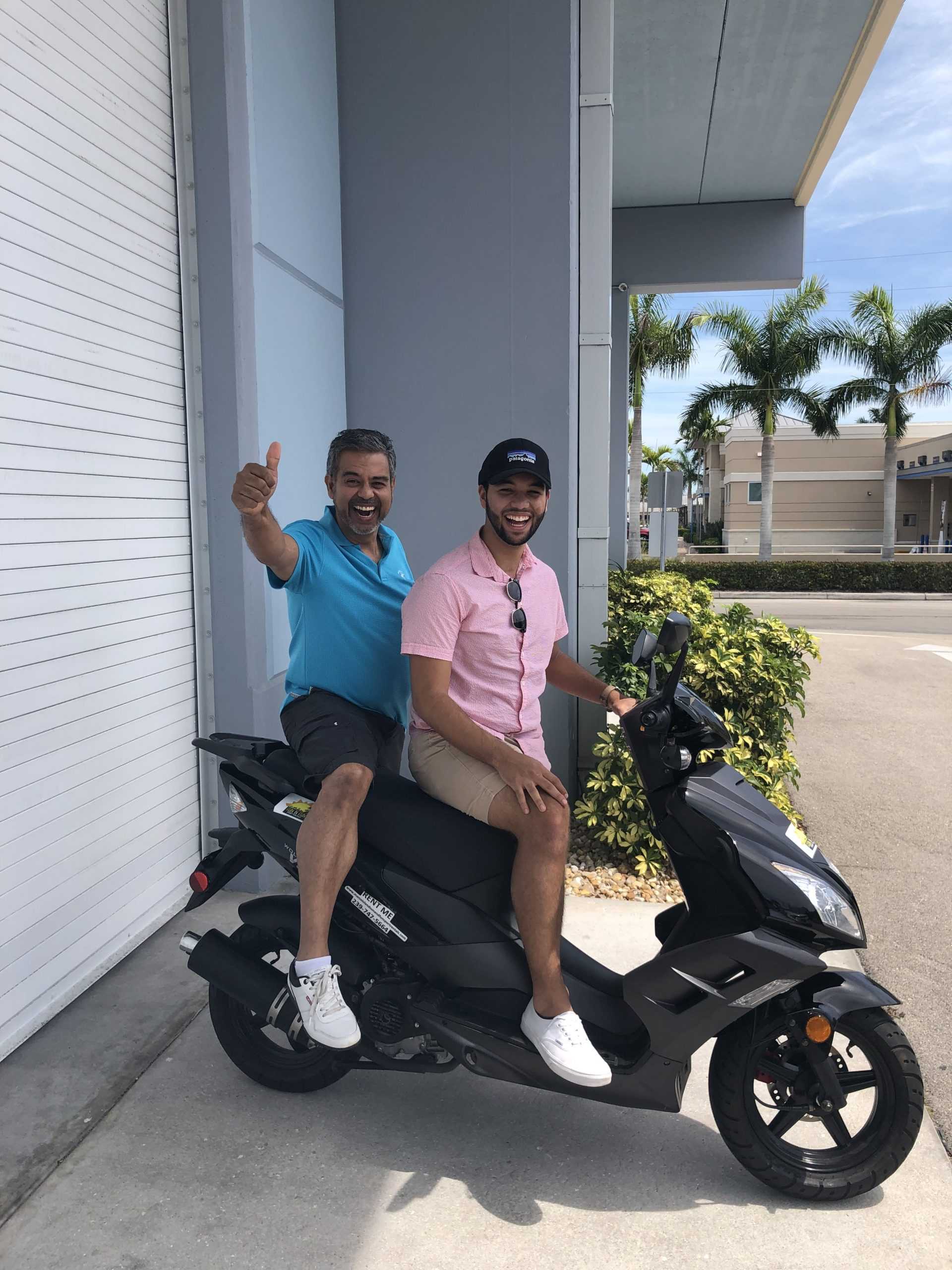 Two men pose and give thumbs up on black scooter on Marco Island
