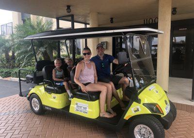 Family of 4 riding yellow golf cart rental