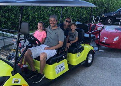 Family of 4 riding a golf cart rental