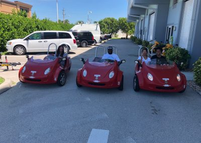 Family of 4 riding 3 red scoot coupes from Sun N Fun Sport Rentals