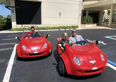 Family of 4 riding 2 red scoot coupe rentals