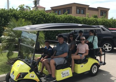 Family of 6 on a yellow golf cart rental from Sun N Fun Sport Rentals
