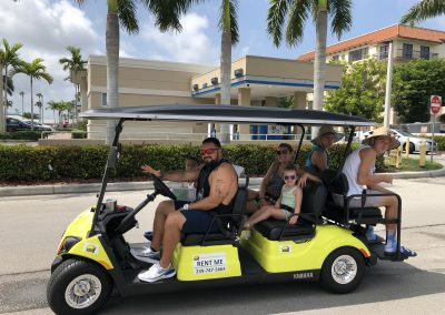 Family of 6 riding yellow golf cart rental