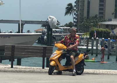 Man in Hawaiian shirt on yellow scooter rental in Marco Island