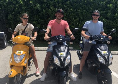 Group of 3 people riding 3 scooter rentals from Sun N Fun Sport Rentals