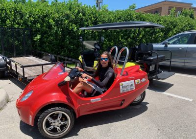 Young person riding a red scoot coupe