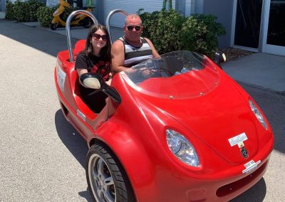 Father and daughter riding a red scoot coupe
