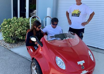 Parent and child riding red scoot coupe next to staff member