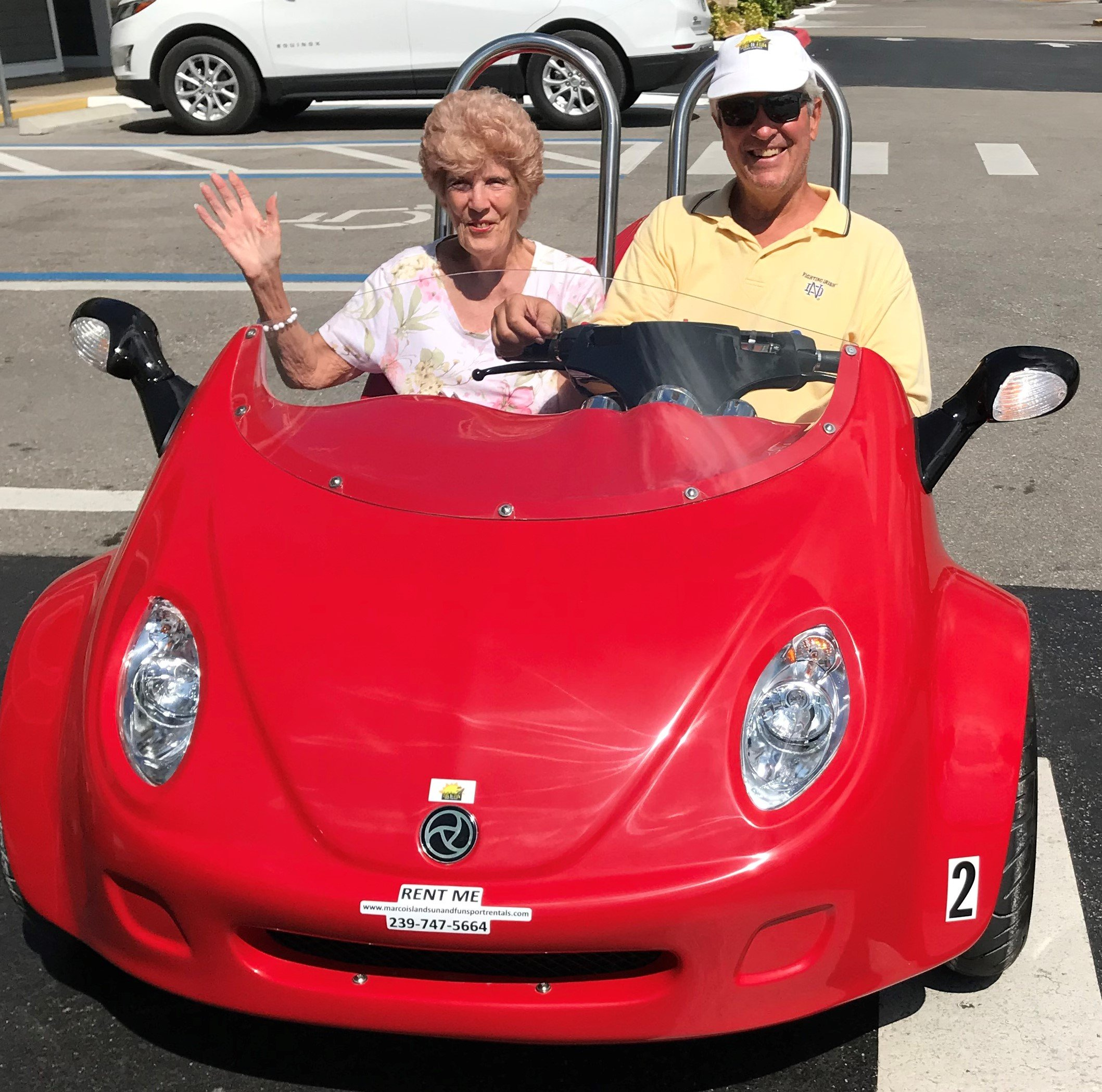 Older couple waves and poses while riding scoot coupe on Marco Island