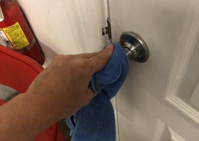 Sun N Fun staff disinfecting a doorknob