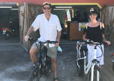 Couple standing outside Fort Myers Beach Sun-N-Fun Sport Rentals on e-bikes