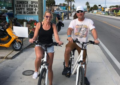 Woman and man riding white ebike rentals