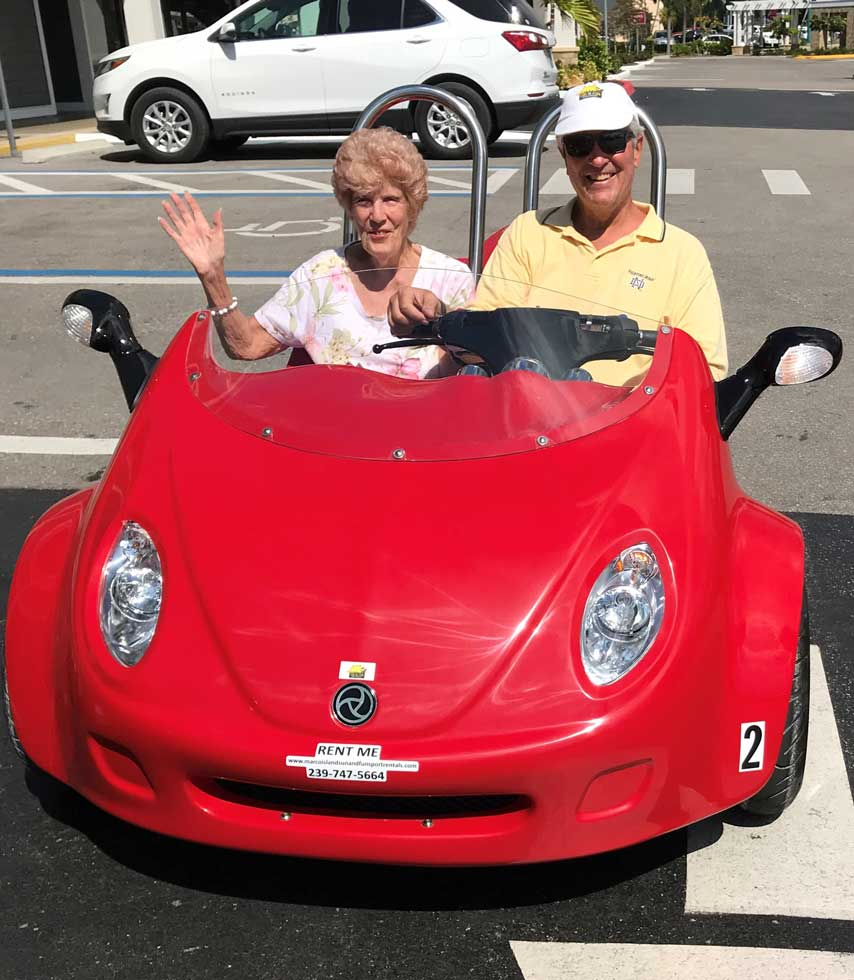 Older couple waving and poses while driving a red scoot coupe
