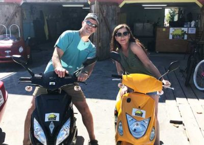 A couple riding scooter rentals